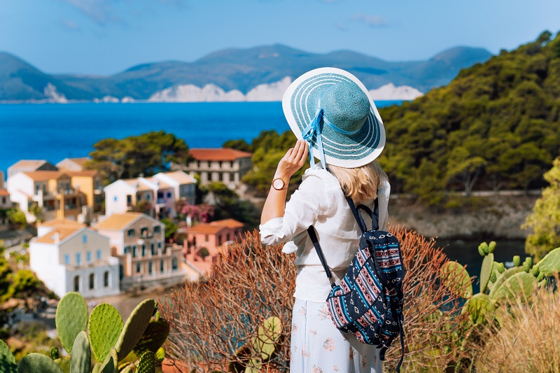 Tourist woman with blue sunhat, white clothes and travel backpack admire view of colorful tranquil village Assos on sunny day. Visiting Kefalonia during summer time on Greece travel vacation